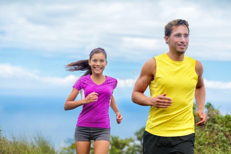 Rinnande uppehälle för lyckligt sportfolk per aktivt liv royaltyfri bild