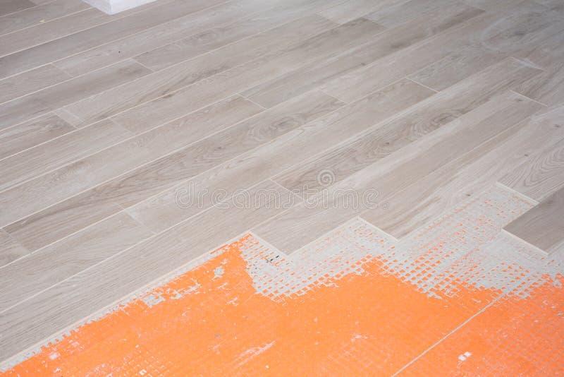 Rinnovamento del pavimento con le piastrelle di ceramica nella progettazione di legno immagini stock