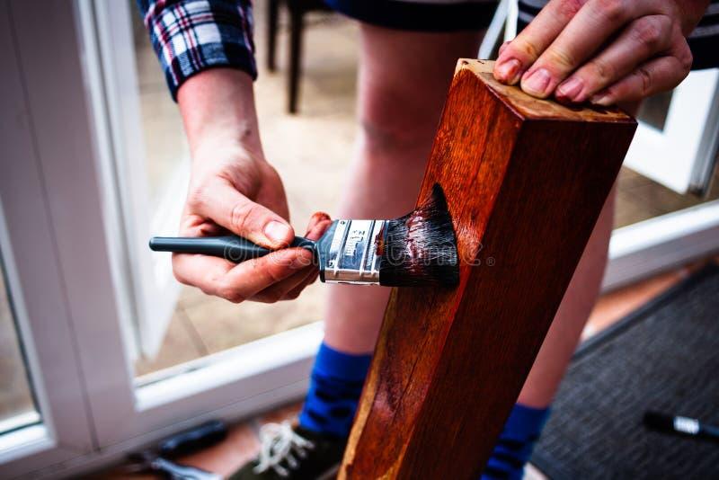 Rinnovamento di vecchia mobilia Concetto di miglioramento domestico con la verniciatura della superficie di legno Vista del primo immagine stock