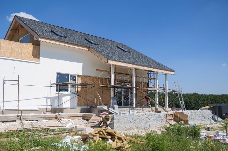 Rinnovi e ripari la parete residenziale della facciata della casa con lo stucco, l'isolamento, intonacare, dipingente la parete C fotografia stock