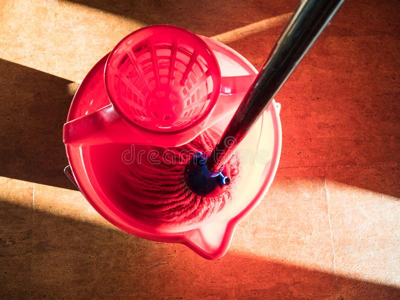 Rinsing out a mop in red bucket of water royalty free stock images