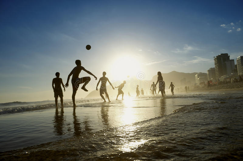 Rio Beach Football Active Silhouettes Playing Altinho. Rio de Janeiro football active silhouettes of Brazilians playing keepy uppy altinho beach soccer on the royalty free stock images