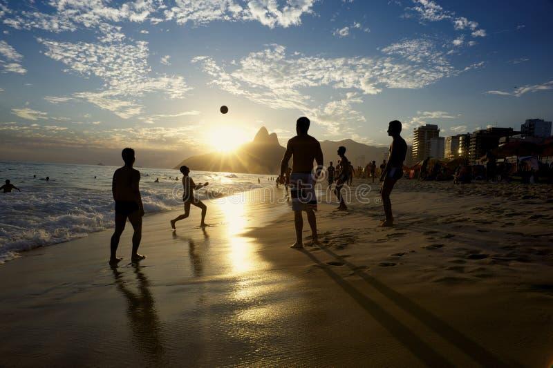 Rio Beach Football Brazilians Playing Altinho. Rio de Janeiro beach football silhouettes of Brazilians playing keepy uppy altinho soccer on the sunset shore at stock photo
