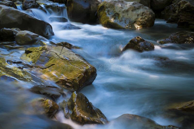 Rio bonito que flui entre rochas foto de stock royalty free