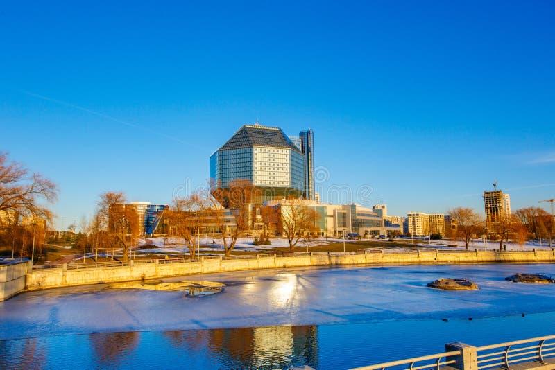 Rio congelado que flui perto da biblioteca pública em Minsk no dia ensolarado foto de stock royalty free