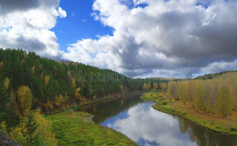Rio contra a floresta do outono com as árvores amarelas e verdes e céu azul colorido brilhante com nuvens foto de stock