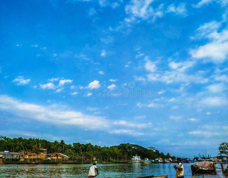 Rio de Bhairav, Noapara, Jashore, Bangladesh: 4 de julho de 2019: A opinião do beira-rio, pessoa, barcos, céu e natural bonitos v imagem de stock