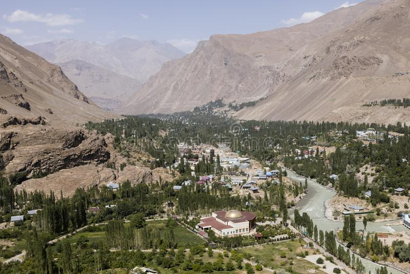 Rio de Gunt com a cidade de Khorog no vale de Wakhan em Tajiquistão com as montanhas de Pamir imagens de stock royalty free