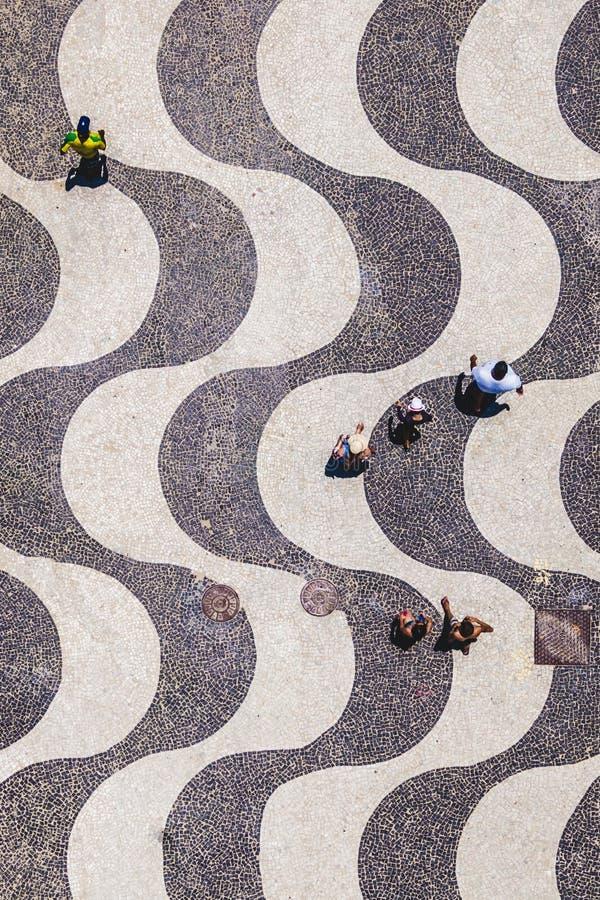 Rio de janeiro, Brasil, opinião superior os povos que andam no passeio icônico da praia de Copacabana imagem de stock