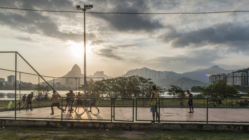 Young men playing football in Rio de Janeiro, Brazil. Rio de Janeiro, Brazil - Dec 19th, 2017: Local Brazilians cariocas play football overlooking Lagoa Rodrigo stock photos