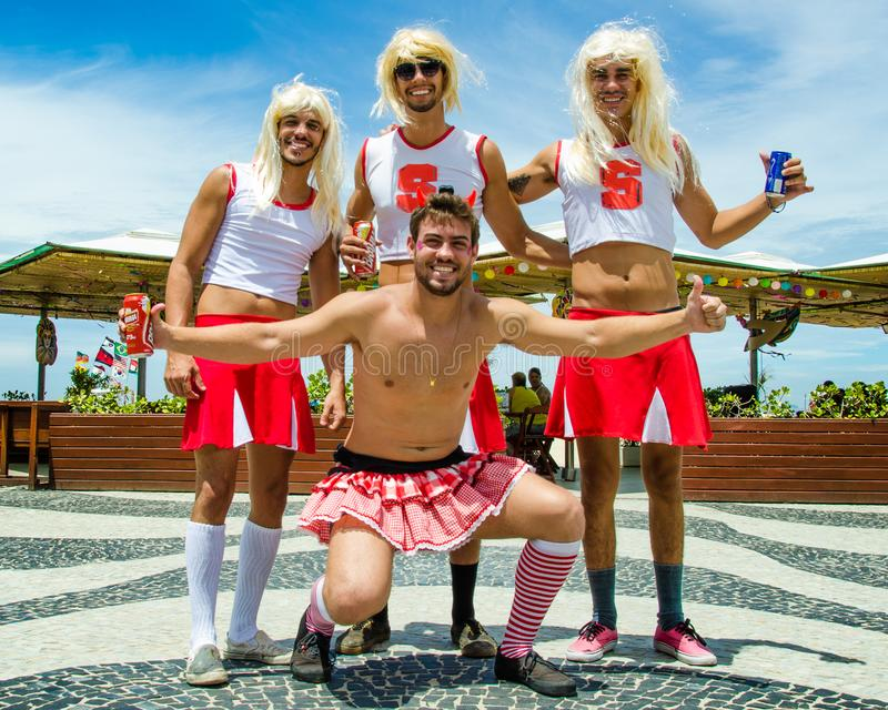Male Carnival revelers are dressed as female cheerleaders stock images