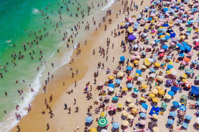 Rio de Janeiro, el Brasil, vista aérea de la playa de Copacabana que muestra los paraguas coloridos y a la gente que se bañan en  fotografía de archivo libre de regalías
