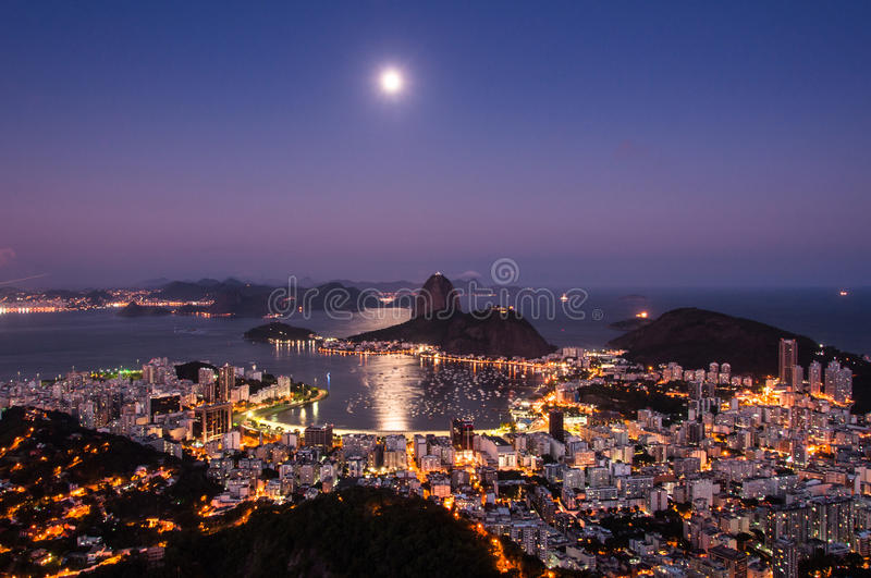 Rio de Janeiro at Night with Moon in the Sky. Night View of Sugarloaf Mountain and Botafogo Neighborhood in Rio de Janeiro with Moon Shining in the Sky stock photo