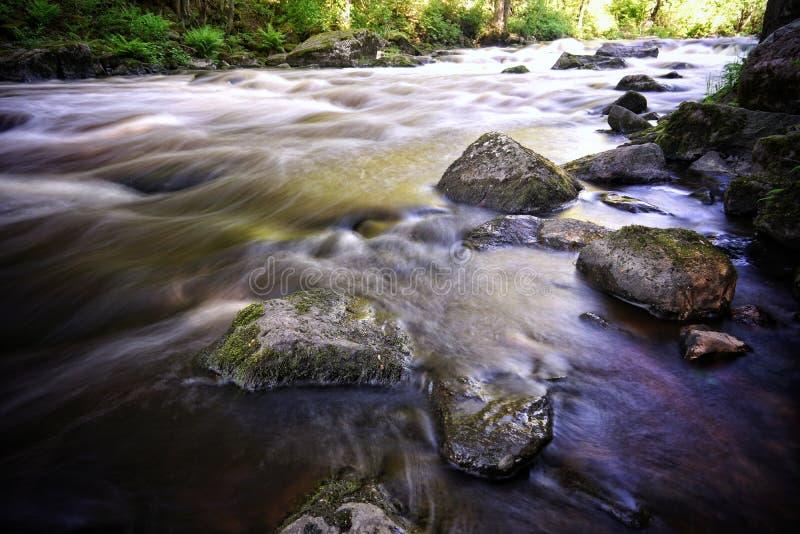 Rio e rochas de fluência bonitos na cena da água fotos de stock royalty free