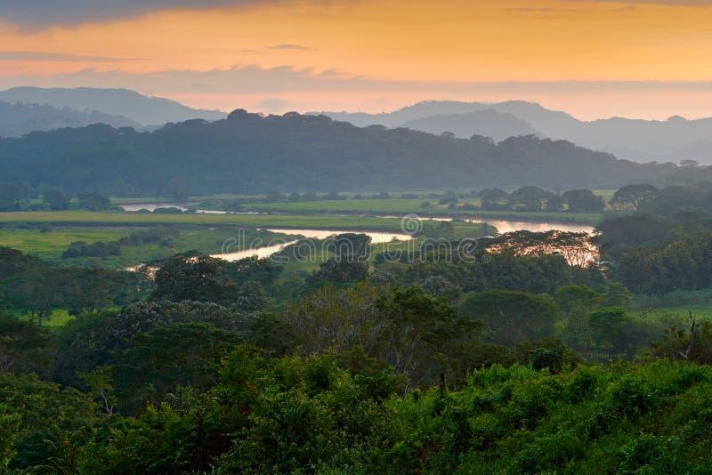 Rio Tarcoles Carara nationalpark, Costa Rica Solnedgång i härligt vändkretsskoglandskap Slingringar av floden Tarcoles Kullar med royaltyfria bilder