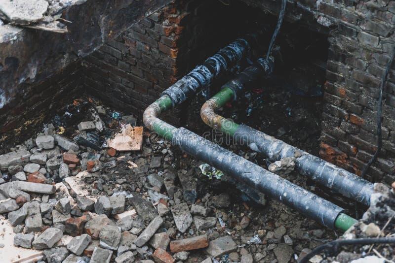 Rioleringsreparatie, de pijpen van het rioolstaal of pijpleiding in baksteendoos voor preventie wordt geopend die stock foto