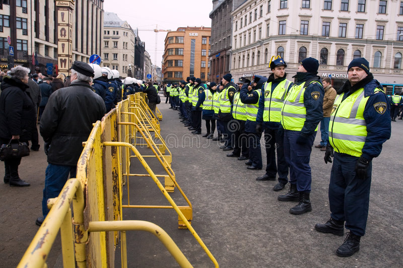 Riot police. Riga, Latvia, March 16, 2009. Crowd control barriers around the Freedom Monument to separate nationalists and anti-fascist demonstrators royalty free stock photography
