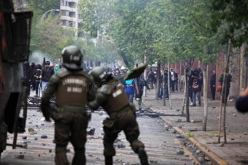 Riot Police in Chile. Santiago, Chile - October 06, 2011: Riot police launching tear gas at protesters during a student strike in Santiago`s Downtown, Chile royalty free stock image