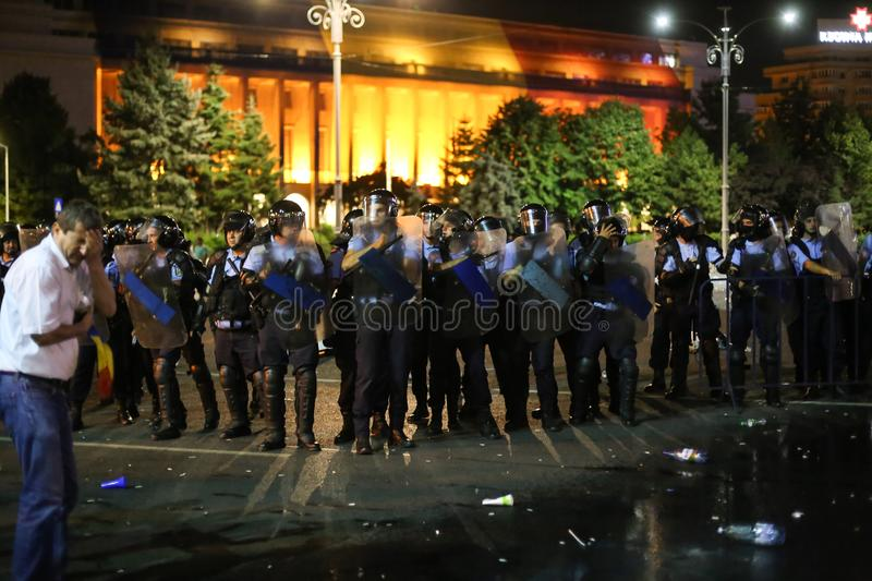 Riot police spray tear gas while scuffling with protesters. BUCHAREST, ROMANIA - August 10, 2018: Riot police spray teargas while scuffling with protesters royalty free stock photos