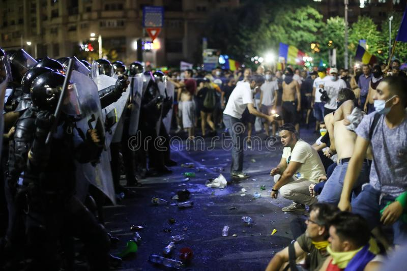 Riot police spray tear gas while scuffling with protesters. BUCHAREST, ROMANIA - August 10, 2018: Riot police spray teargas while scuffling with protesters royalty free stock image