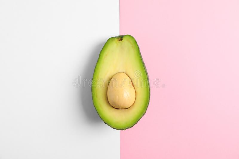 Rip cut avocado on two tone background. Space for text stock photos