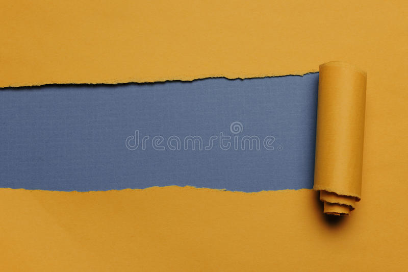 Rip Paper. Rip Yellow Paper and blue background with space for text stock photography