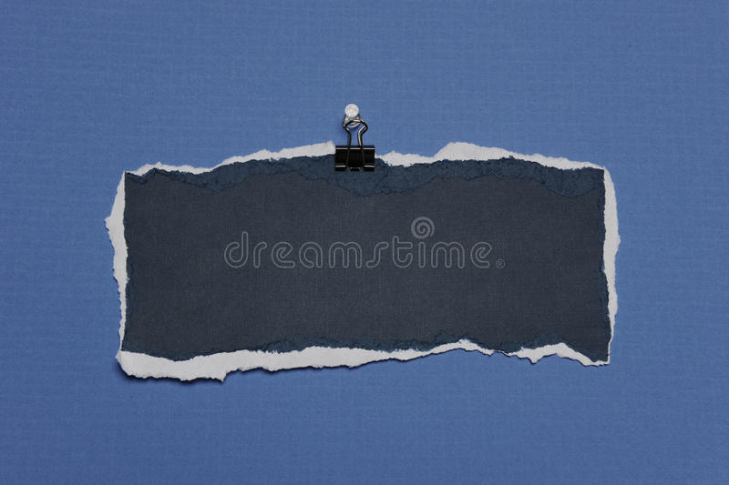 Rip Paper with empty space for text. Piece of Rip Paper with white edges on a clip against a blue background royalty free stock photos