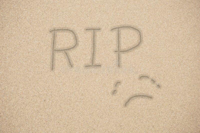 RIP, rust in vrede, die op zand hoanwriting stock afbeelding