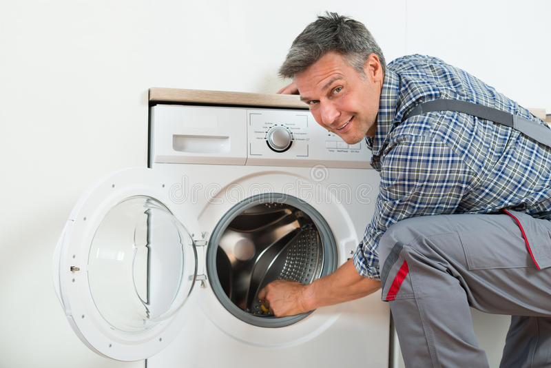 Riparatore Checking Washing Machine a casa fotografie stock
