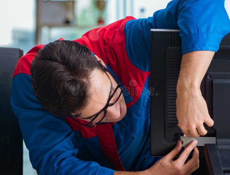 Riparatore del computer che lavora a riparare computer nell'officina dell'IT fotografia stock libera da diritti