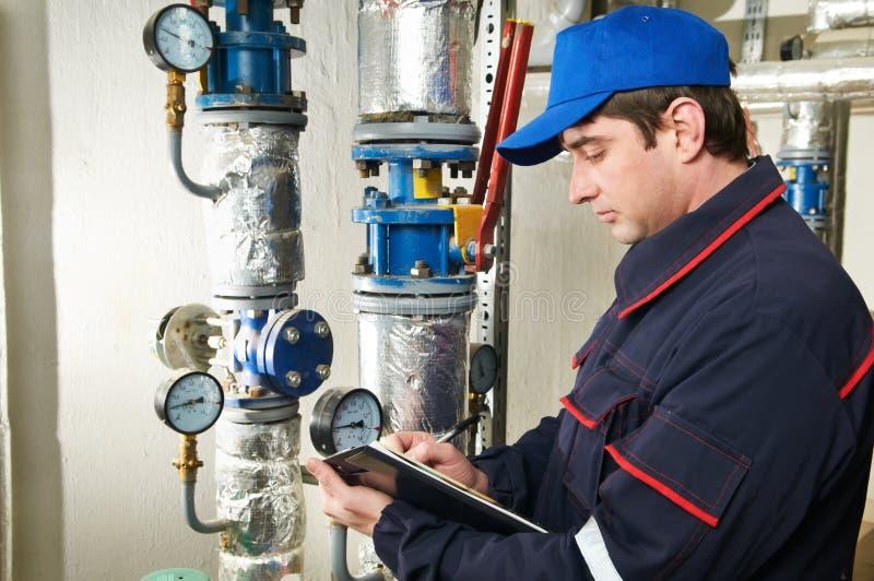 Riparatore dell'assistente tecnico del riscaldamento nel locale caldaie immagini stock libere da diritti