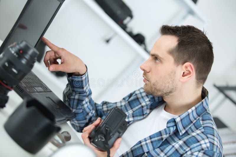 Riparatore della macchina fotografica che esamina computer portatile fotografia stock libera da diritti