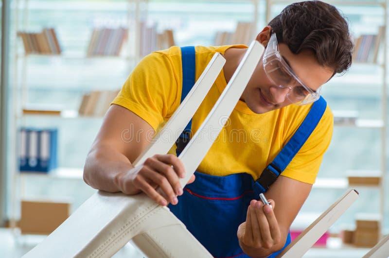 Riparatore della mobilia che lavora a riparare la sedia fotografie stock