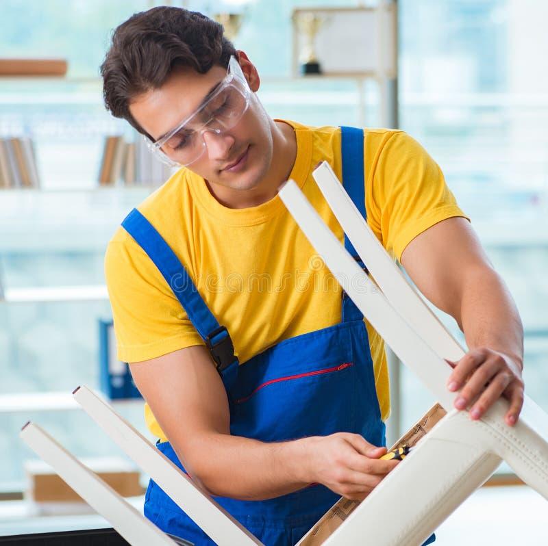 Riparatore della mobilia che lavora a riparare la sedia immagini stock libere da diritti
