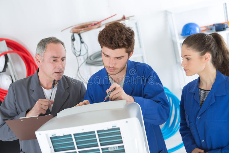 Riparatori del condizionamento d'aria che discutono problema con l'unità del compressore immagine stock