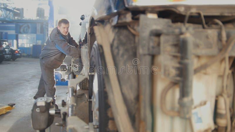 Riparazione automobilistica dell'automobile - il lavoratore è veicolo commovente per il crollo del ` s della ruota di convergenza fotografia stock