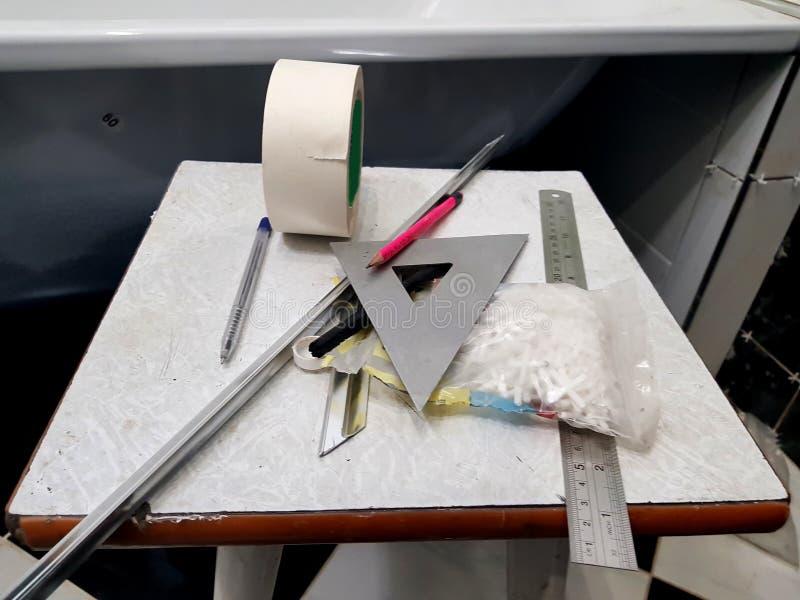Riparazione - costruzione con gli strumenti, misura di nastro, matita, penna, indicatore, nastro protettivo, triangolo, angolo, a fotografia stock