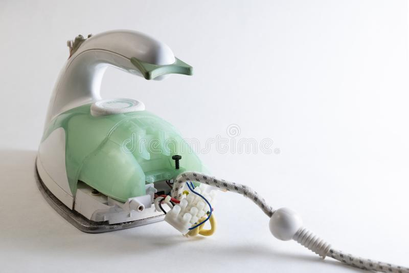 Riparazione degli elettrodomestici Ferro da stiro verde smontato Dispositivo elettrico né un fondo bianco Copi lo spazio fotografia stock