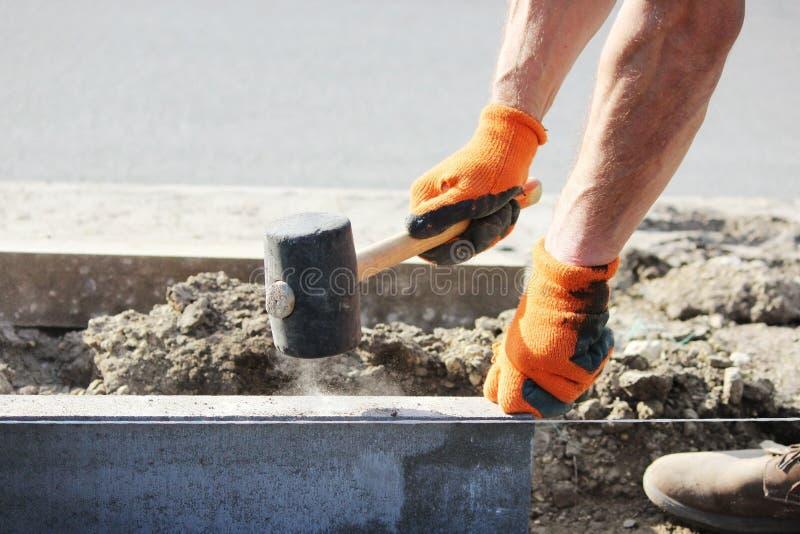 Riparazione del marciapiede I muratori lavoranti professionisti in camici trasmettono i bordi a porre le lastre per pavimentazion immagine stock