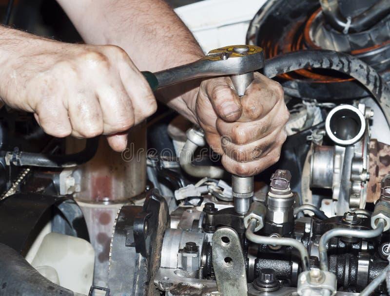 Riparazione del motore Lo strumento in mani immagini stock