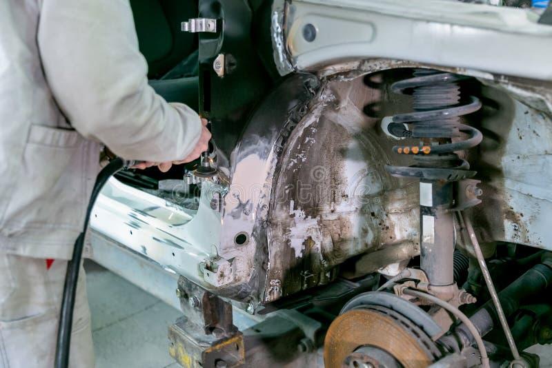 Riparazione dell'automobile nel servizio dell'automobile Carrozzeria del riparatore del lavoratore del meccanico ed automobile di fotografie stock