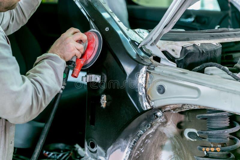 Riparazione dell'automobile nel servizio dell'automobile Carrozzeria del riparatore del lavoratore del meccanico ed automobile di fotografia stock libera da diritti