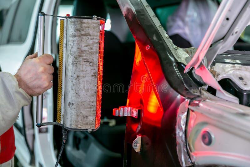 Riparazione dell'automobile nel servizio dell'automobile Carrozzeria del riparatore del lavoratore del meccanico ed automobile di fotografia stock