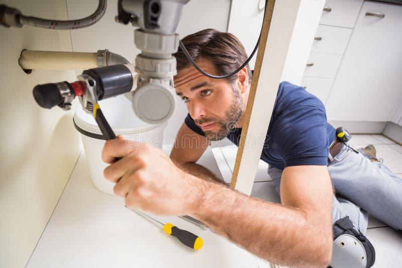 Riparazione dell'idraulico sotto il lavandino fotografia stock