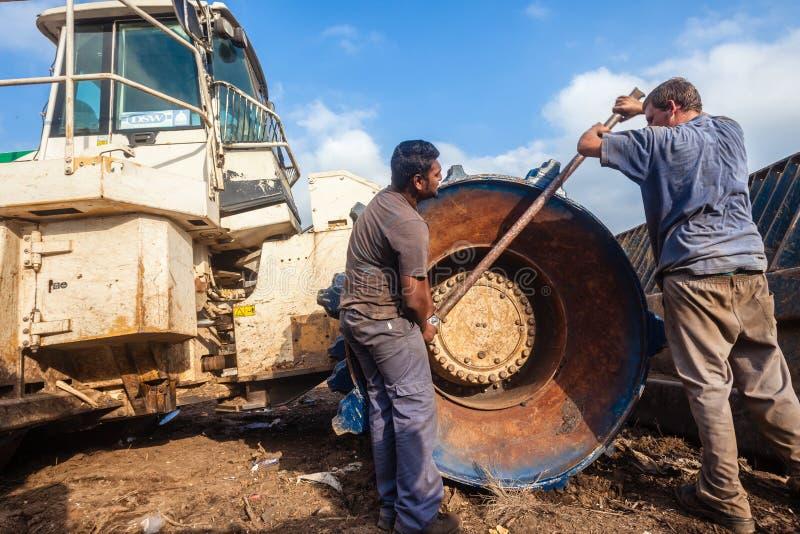 Riparazione della ruota del macchinario pesante dei meccanici di ingegneria immagini stock libere da diritti