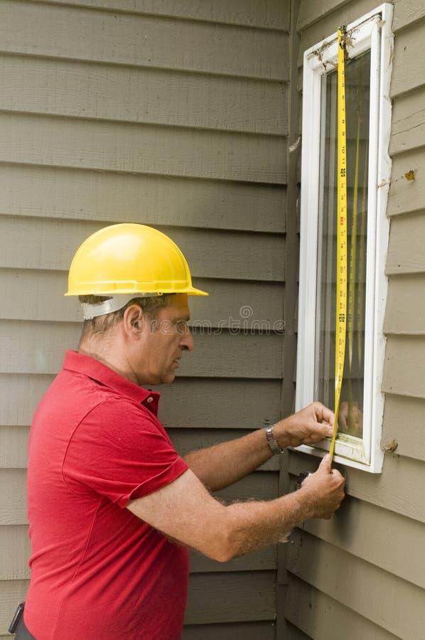 Riparazione di misurazione della finestra del carpentiere fotografia stock