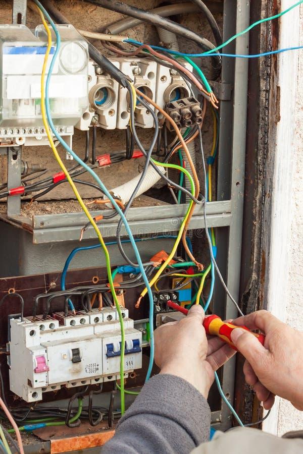 Riparazione di vecchia apparecchiatura elettrica di comando elettrica Un elettricista sostituisce i vecchi dispositivi elettrici  immagine stock libera da diritti