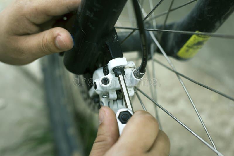 Riparazione ed adeguamento dei freni a disco su un mountain bike, strumenti della bicicletta fotografia stock libera da diritti