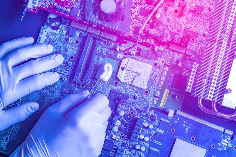 Riparazione matrice le parti del computer, pulenti il bordo facendo uso del tampone f dell'ovatta immagine stock