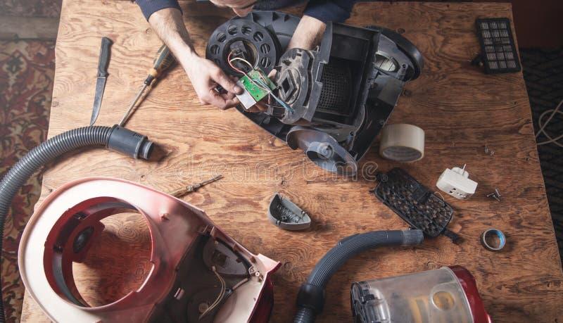 Riparazioni dell'uomo dell'aspirapolvere riparare fotografie stock libere da diritti